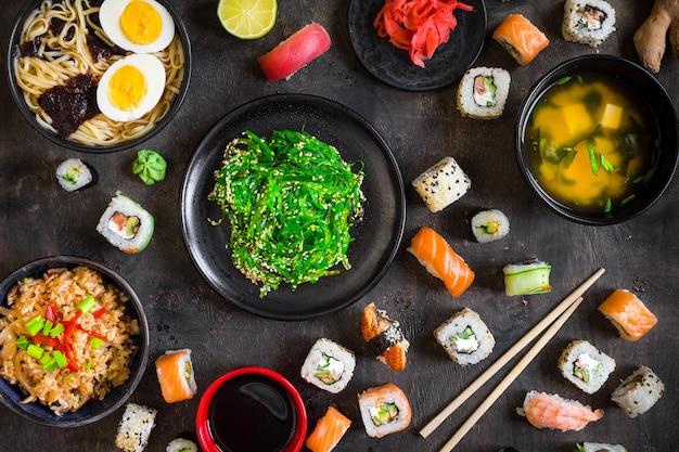 어두운 배경에 초밥과 전통적인 일본 음식을 제공하는 테이블.