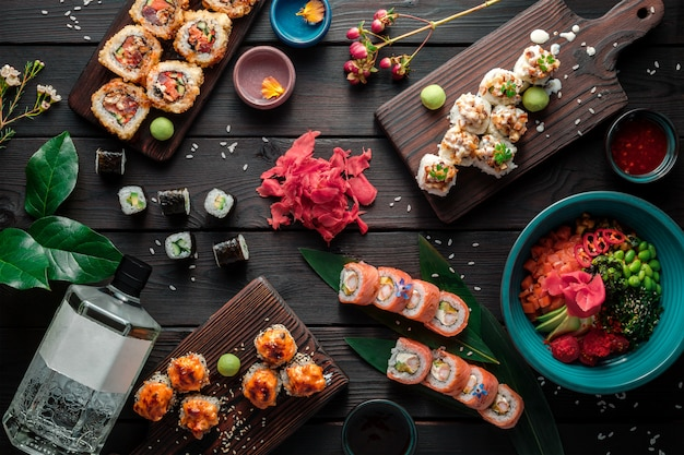 Table served with sushi, rolls and traditional japanese food on dark background. top view.