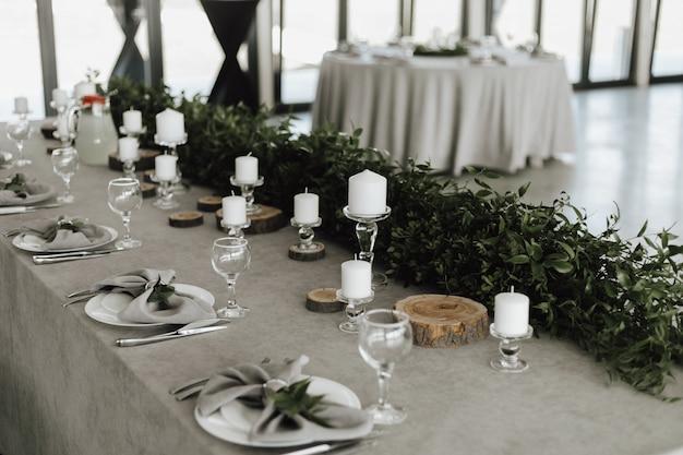 Servizio da tavola, decorazione con verde e candele bianche sul tavolo grigio