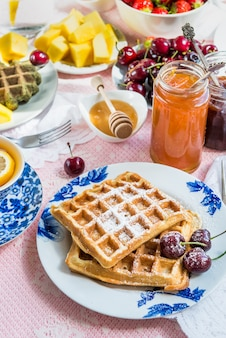 Table set for breakfast with waffles and berries