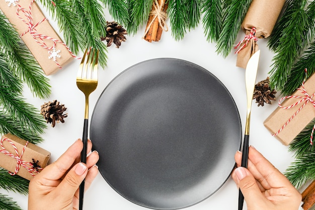 Table set for christmas party woman hands hold gold cutlery over black empty plate