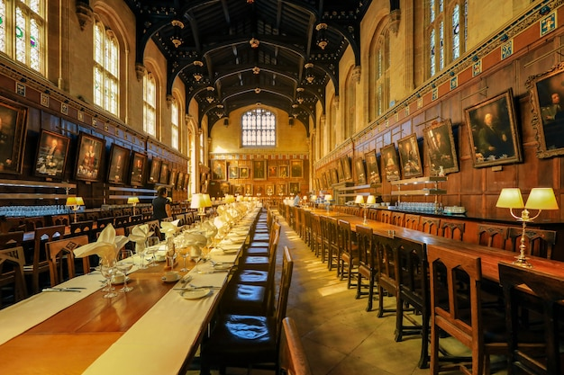 Table set for dinner at the great hall of christ church,  the hall was replicated at film studios as the grand dining hall at harry potter's hogwarts school.