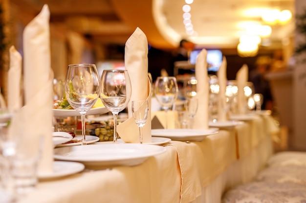 イベントパーティーや宴会用のテーブルセット。ガラスとナプキンに焦点を当てる