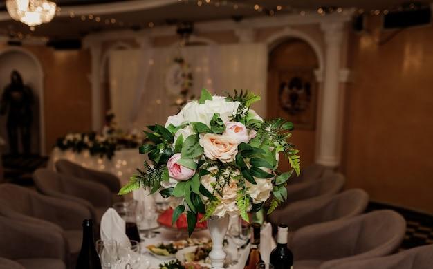레스토랑에서 꽃 구성으로 저녁 식사를 위한 테이블 세트, 고급스러운 인테리어 배경. 결혼식 우아한 연회 장식