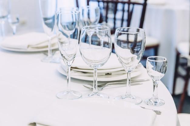 レストラン、豪華なインテリアでナプキングラスとディナーのテーブルセット
