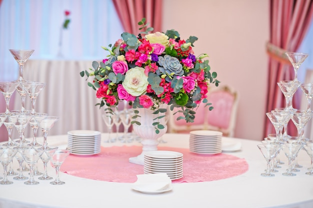 Table set at the wedding banquet in the restaurant, classic style with white tablecloths and napkins, vases with flowers.