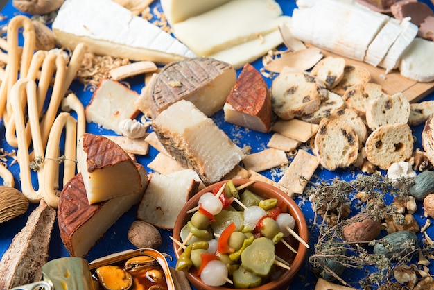 Table set with an aperitif consisting of different foods cheeses and cans of pickles
