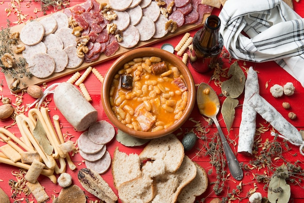 Table set with an asturian bean stew from spain and several appetizer starters with sausages