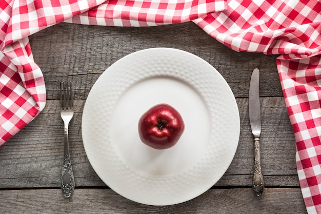 Table set with red apple on white plate with knife and fork with red checkered napkin.