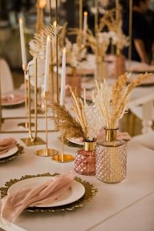 豪華な結婚式のテーブルセッティングとテーブルの上の美しい花。結婚式の装飾、花、ピンクとゴールドの装飾、キャンドル。お祝いのテーブルの装飾。
