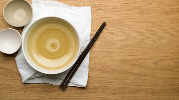Table setting background, mock up ceramic bowls, table cloth and chopsticks on wooden table, copy space