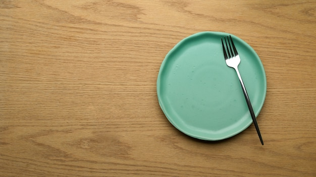 テーブル設定の背景、セラミックプレートのモックアップ、木製テーブルのフォークとコピースペース、上面図