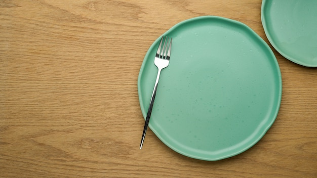 Table setting background, mock up ceramic plates, fork and copy space on wooden table, top view, clean plates