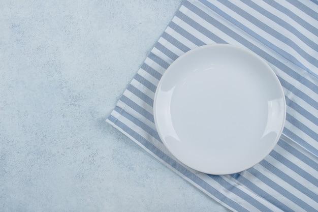テーブル設定の背景。青い縞模様のテーブルクロスと青い石のテーブルの上の白いプレート