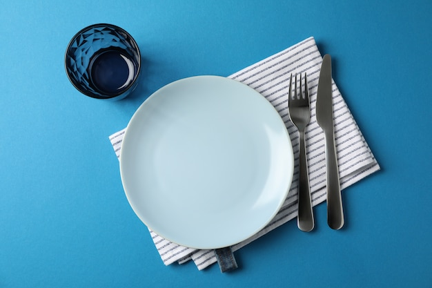 Table setting on blue background, top view