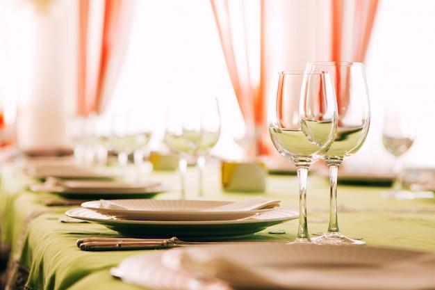 테이블 세팅. 식탁은 녹색 식탁보로 덮여 있습니다. 녹색 식탁보에 하얀 접시입니다. 테이블에 유리 받침 달린 컵. 주방용 칼. 포크, 나이프, 접시, 유리.