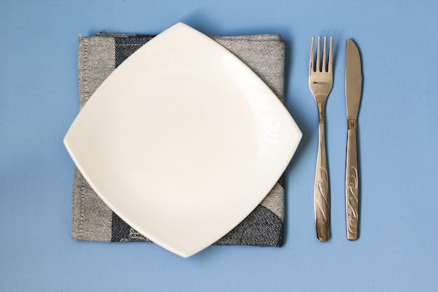 테이블 세팅. 빈 접시, 나이프, 포크, 냅킨. 복사 공간이 있는 평면도 및 평면도