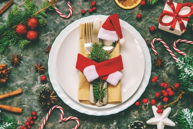 クリスマスの装飾のためのテーブルセッティング。セレクティブフォーカス。ハリデー。 Premium写真