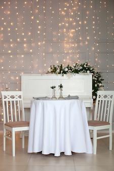 クリスマスディナーのテーブルセッティング。冬の装飾と白いキャンドルの中でテーブルクロスでお祝いテーブルの設定。クリスマス家族ディナーコンセプト。装飾が施された美しいクリスマステーブルの設定