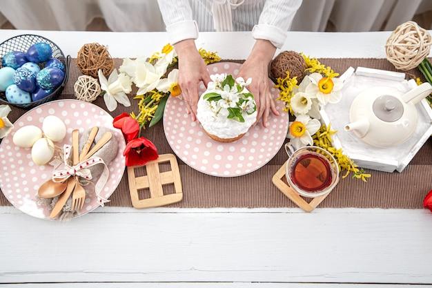 부활절 휴가를위한 테이블 설정입니다. 차, 수제 케이크, 계란 및 꽃 나무 테이블에 닫습니다.