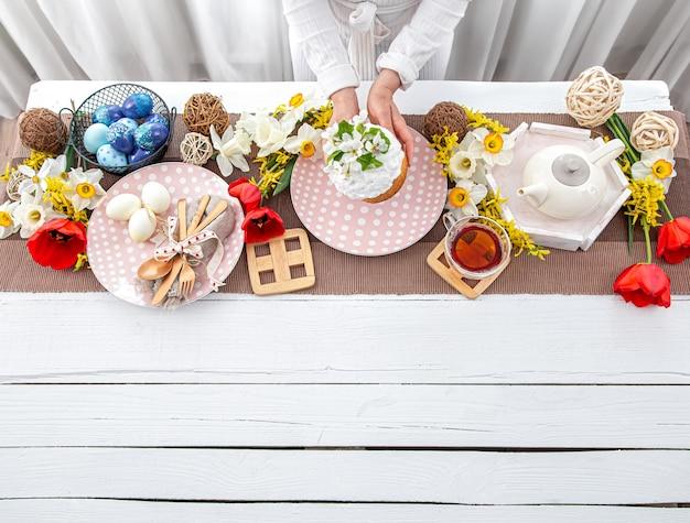 부활절 휴가를위한 테이블 설정입니다. 차, 수 제 케이크, 계란 및 꽃 나무 테이블 복사 공간에.