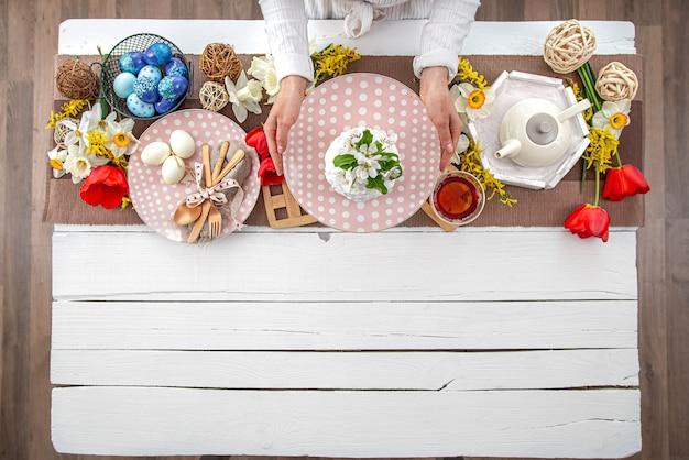 부활절 휴가를위한 테이블 설정입니다. 차, 수 제 케이크, 계란 및 꽃 나무 테이블에.