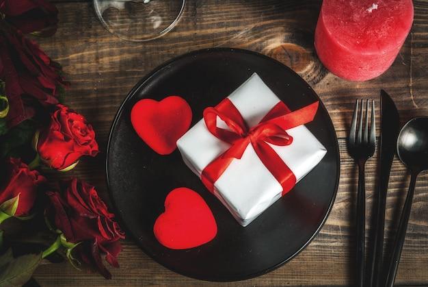 バレンタインデーのテーブルセッティング。赤いバラの花束、赤いリボン、ギフトボックス、赤いハート、キャンドル、プレート、フォーク、スプーン、ナイフと結び付けます。木製のテーブルの上