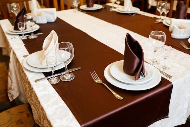 Сервировка стола в ресторане. стакан, тарелка, вилка, нож