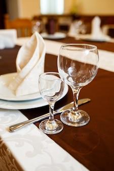レストランのテーブルセッティング。ガラス、プレート、フォーク、ナイフ
