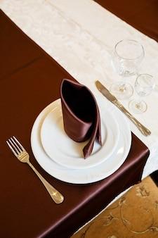 레스토랑에서 테이블 설정입니다. 유리, 접시, 포크, 나이프