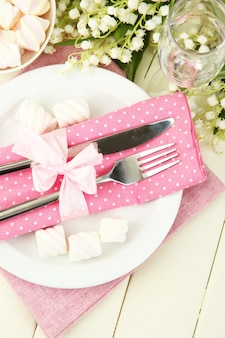 Сервировка стола в белых и розовых тонах на цветной деревянной поверхности