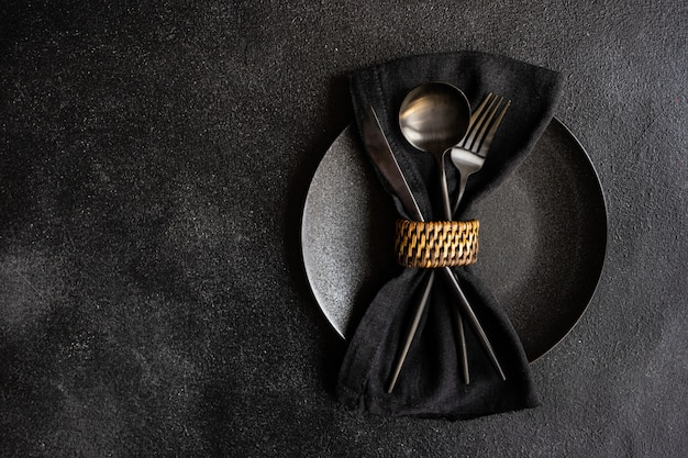 Table setting in minimalistic style with black stylish cutlery on black concrete table with copy space