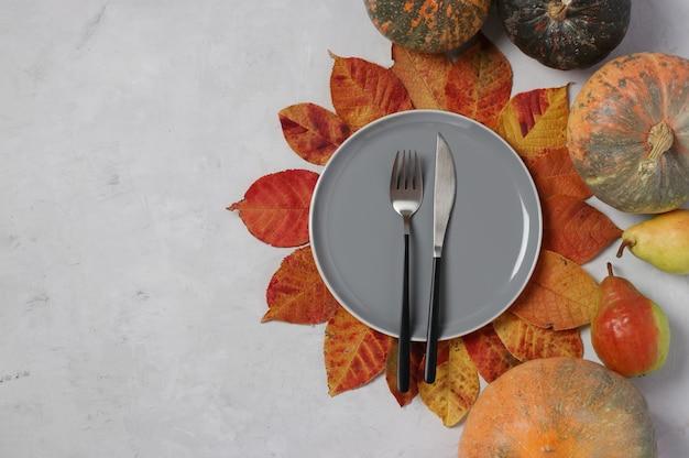 추수 감사절에 테이블 설정은 회색 배경에 호박, 배, 화려한 잎을 장식했습니다. 텍스트를 위한 공간입니다.