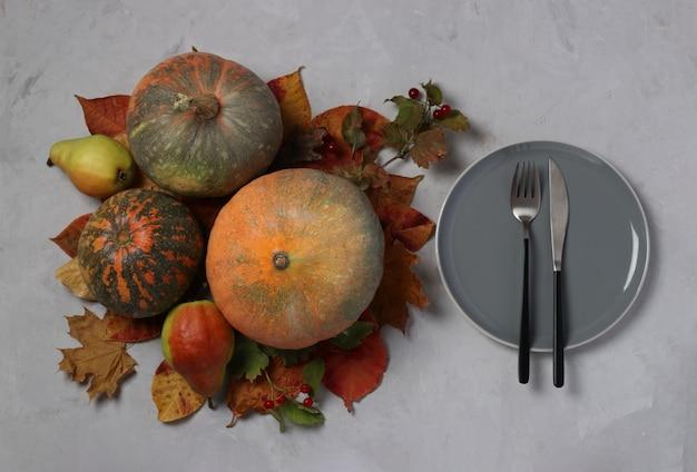 Сервировка стола в день благодарения украшена тыквой, калиной, грушами и разноцветными листьями на сером. вид сверху