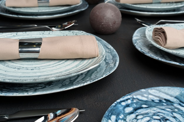 Table setting. plates with abstract pattern on black table