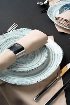 テーブルセッティング。黒いテーブルに抽象的なパターンを持つプレート