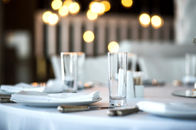Table setting at a restaurant. clean glass cup close up. details of the banquet table.
