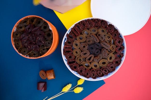 Сервировка стола, романтическое чаепитие со сладостями в коробке, вид сверху, никто. роскошное столовое серебро на красной скатерти, посуда на открытом воздухе.