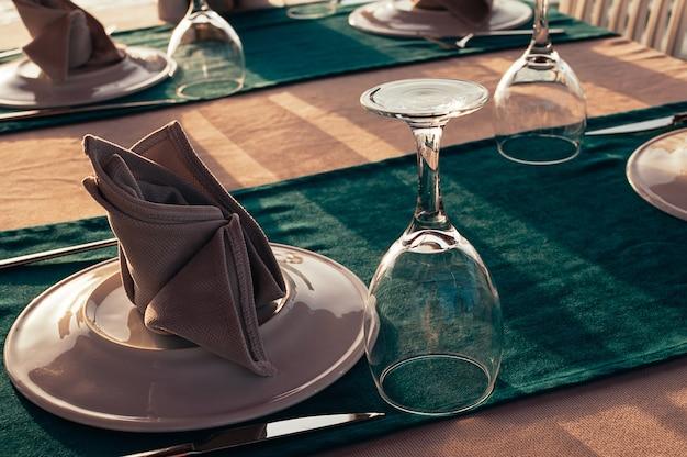 Сервировка стола в ресторане на открытом воздухе, вечерние лучи солнца