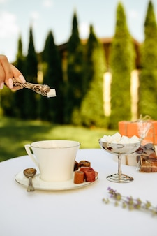 Сервировка стола, чаепитие, женская рука кладет сахар в чашку, вид сбоку. роскошное столовое серебро на белой скатерти, посуда на открытом воздухе.