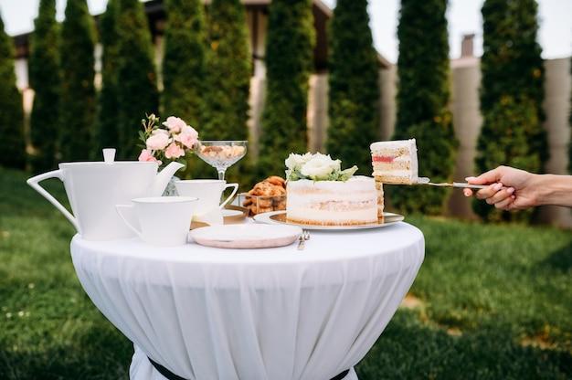 Сервировка стола, чаепитие, женская рука принимает крупный план торта, вид сбоку. роскошное столовое серебро на белой скатерти, посуда на открытом воздухе