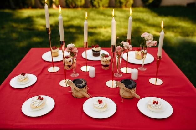 Сервировка стола, чаепитие со сладостями и медом, никто. роскошное столовое серебро на красной скатерти, посуда на открытом воздухе.