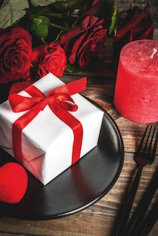 Table setting for valentine's day. bouquet of red roses, tie with a red ribbon, gift box, red hearts, candle, plate, fork, spoon and knife. on a wooden table