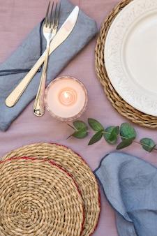 Table setting white plate, rattan coasters, lit candle, cutlery, napkins eucalyptus