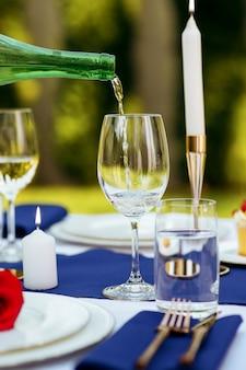 テーブルセッティング、ワインはボトルからワイングラス、キャンドル、プレートのクローズアップの花に注がれています。誰もいません。高級銀器と白いテーブルクロス、屋外の食器