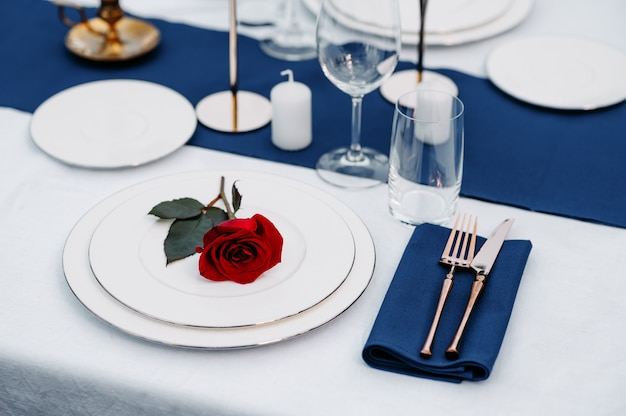 テーブルセッティング、ワイングラス、キャンドル、プレートのクローズアップの花、誰も。高級銀器と白いテーブルクロス、屋外の食器