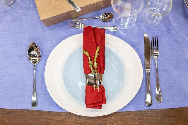 파란색 식탁보, 흰색 및 파란색 접시, 강철 홀더에 빨간색 냅킨, 강철 가전 제품, 유리 잔이 있는 테이블 설정. 평면도, 클로즈업