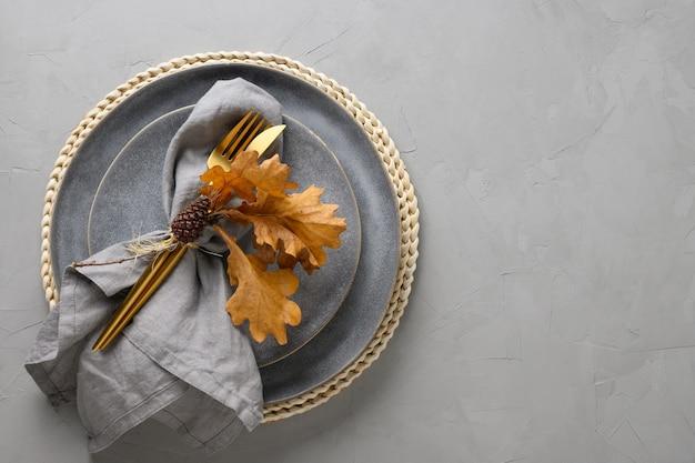 Сервировка стола с осенними дубовыми листьями и золотыми столовыми приборами на сером.