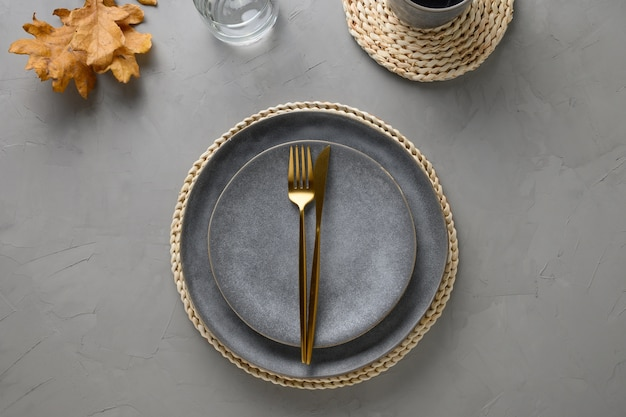 Table setting with autumn oak leaves and golden cutlery on grey.