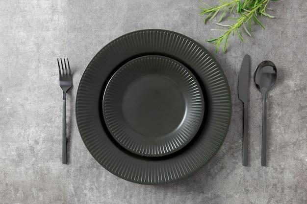 ハーブと暗い石のテーブルの上の黒いプレートとカトラリーのテーブルセッティング
